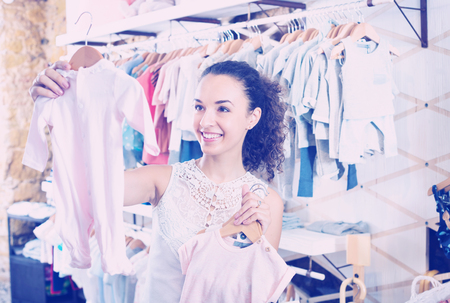 Young cheerful woman choosing baby pajamas in the kids apparel boutique