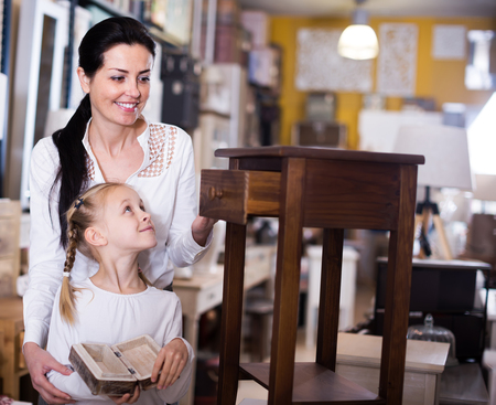 Smiling female with daughter standing with curbstone in furniture store
