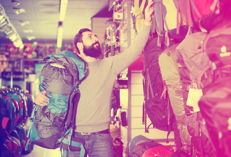 Young male choosing new backpack in sports equipment store