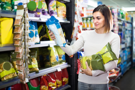 Young spanish woman choosing delicious snacks in supermarket Stockfoto