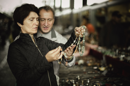 Mature woman and her husband are visiting open air market of old things and shopping outdoors
