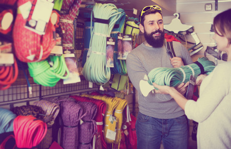 Smiling guy and woman choosing climbing equipment in sports equipment store