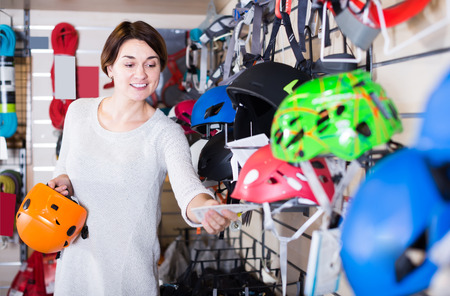 Smiling female customer deciding on new helmet in sports equipment store
