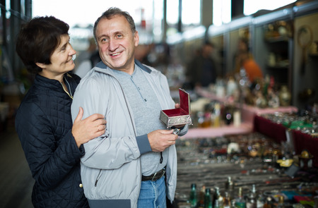 positive adult man and woman are choosing jewelry box at the market of old things.