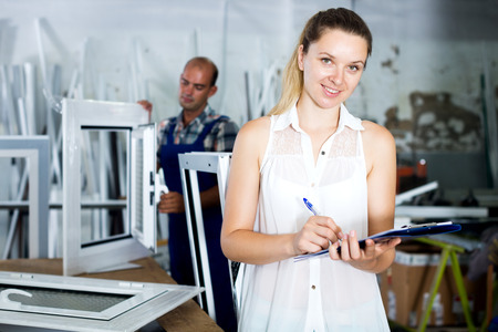 Happy female supervisor checking quality of work on assembling PVC windows in factory Stock Photo