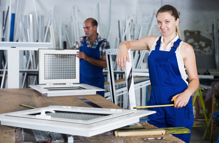 Smiling workwoman in overalls using measuring tape and standing with pvc window