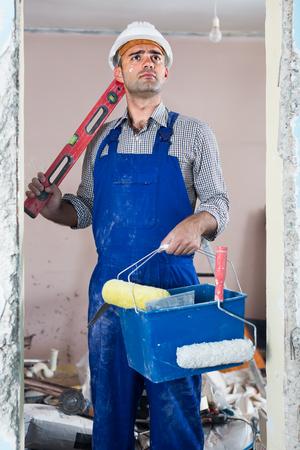 Portrait of builder man in uniform standing with spirit level and bucket indoors Stock Photo