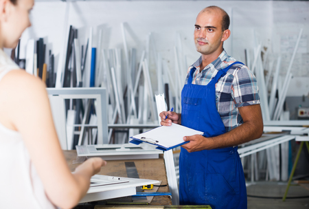 happy american assembler of plastic windows with clipboard in hands talking to female manager at factory Stock Photo