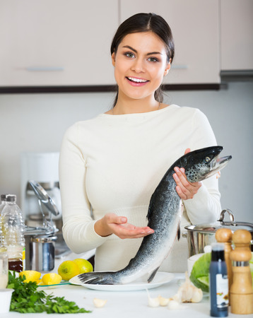Positive woman in white sweater cleaning fresh rainbow trout