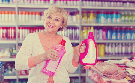 Positive woman consumer with household chemical products for washing indoors