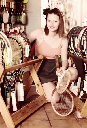 Smiling girl examines a range of wooden badminton rackets in the store