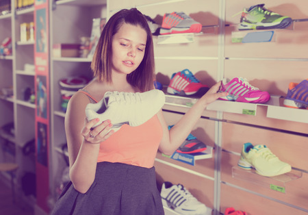 Smiling teenage girl buying professional shoes in sport shop