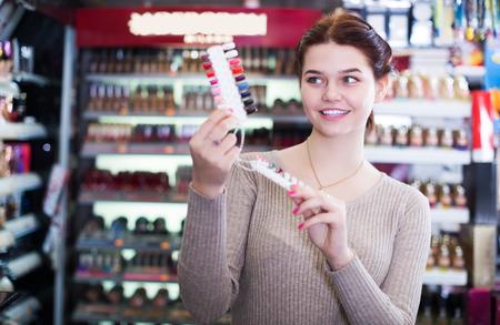 Positive seller demonstrating assortment of cosmetics shop