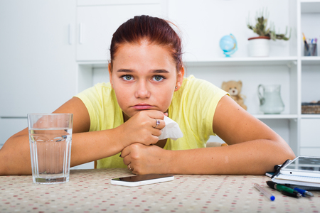 Portrait of teenager girl sadly waiting for call sitting indoors
