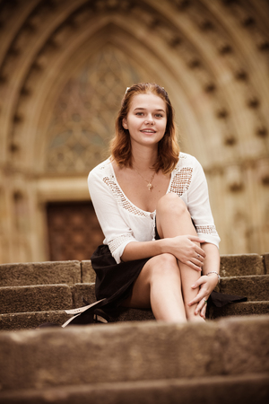 Young positive female sitting on stone stairs at the street