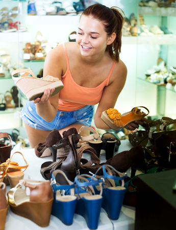 Positive teenager girl searching for pair of new shoes in fashion shop