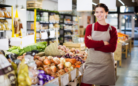 Smiling young saleswoman offering large onion in vegetable section of foodshop Archivio Fotografico