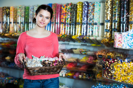 Young smiling saleswoman holding wicker basket with chocolates and many sweets
