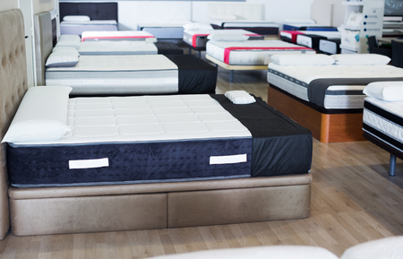 new style mattresses on the beds in the store. Foto de archivo