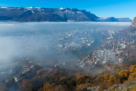Picturesque mountains landscape of snowy Alps and downtown of Grenoble under clouds in sunny winter day Stock Photo