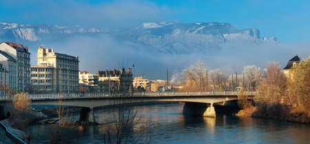 Panoramic view of Grenoble with Isere river against backdrop of mountains in sunny winter day, France