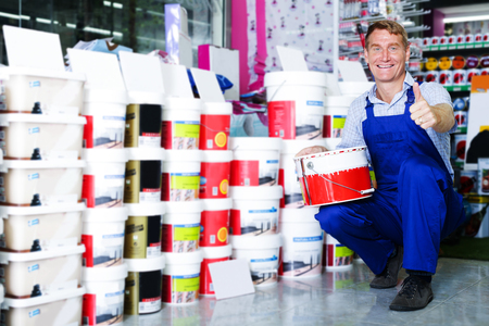 glad male seller in coveralls picking paint tin in household store