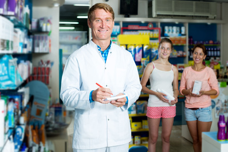 Portrait of glad man druggist in white coat working in pharmacy