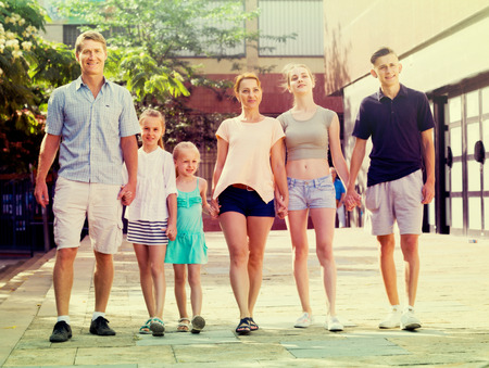 family of six people happily walking together in summer city