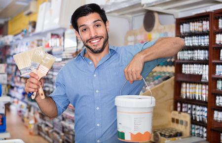 Satisfied young cheerful  man standing amongst racks in paint store with brushes and paint