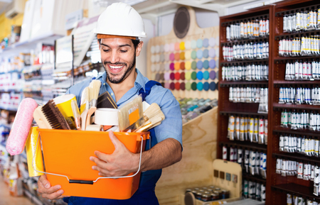 Happy cheerful positive smiling workman holding basket with picked tools in paint store