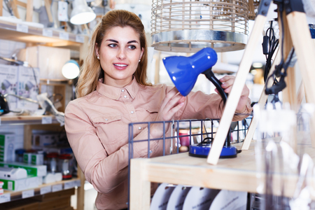 Positive female housewife buying table lamp in store