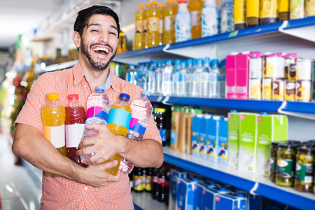 Portrait of smiling american  man customer who is standing with drinks in supermarket.