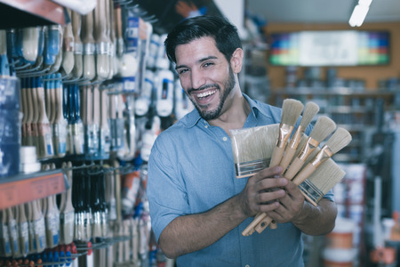 Satisfied young man standing amongst racks in paint store selecting brushes Stock Photo