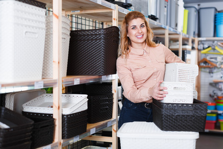 Modern female housewife buying plastic baskets for home in store