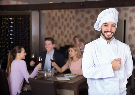 Portrait of confident smiling chef standing in restaurant hall