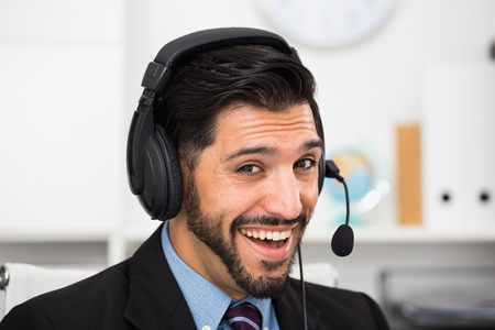 Smiling man dispatcher is speaking with client on his work place. Stock Photo