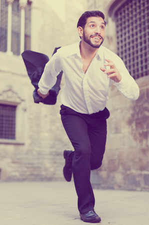 Expressive young man running past old city buildings Stock Photo