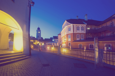 View of Sibiu streets on background with tower of cathedral in night lights, Romania