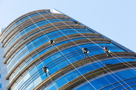 Several industrial alpinists cleaning windows of glass skyscraper Stock Photo