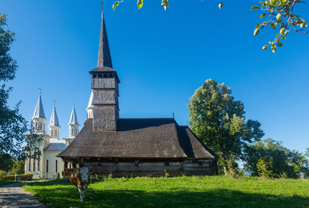 Traditional ancient wooden church with new building behind in Remetea Chioarului, Maramures, Romania 版權商用圖片
