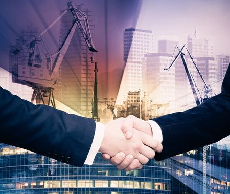 Double exposure of businessmen handshake on industrial business background