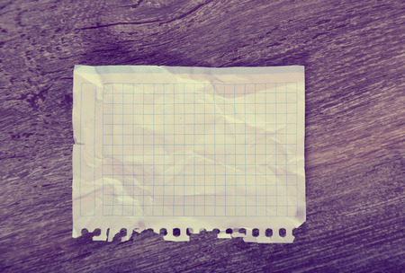 Crumpled notebook sheet in cage on table