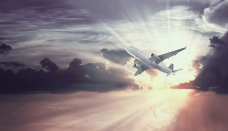 Airplane soaring high in sunny blue sky with white clouds Archivio Fotografico
