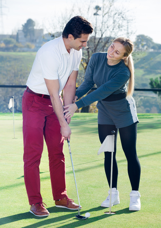 Adult golf trainer showing male player how to hit ball rightly