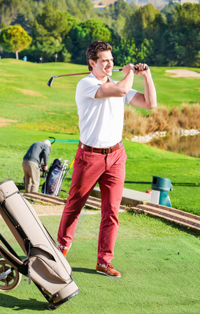 Glad male golf player made successful hit at golf course Stock Photo