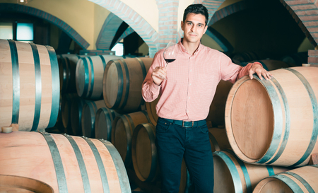Young male owner of winery standing with wine in cellar