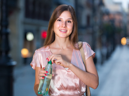 Young smiling female drinking water in historic city center Stock Photo