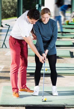 Happy man golf trainer showing female player how to hit ball rightly