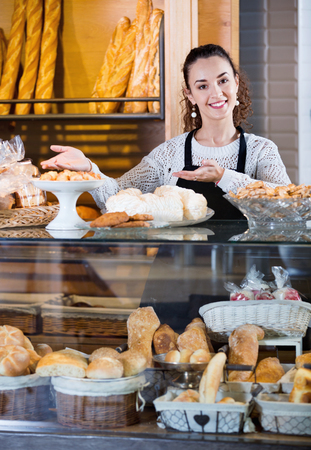 Smiling shopgirl working in bakery with bread and different pastry