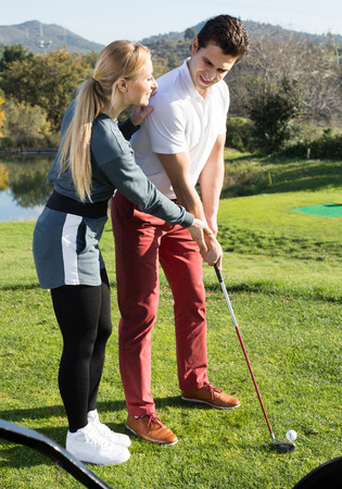 Pretty golf trainer showing male player how to hit ball rightly